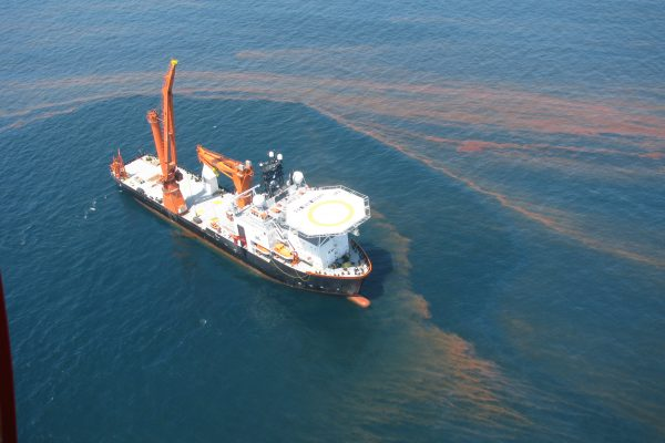 Large vessel in gulf surrounded by oil slick.